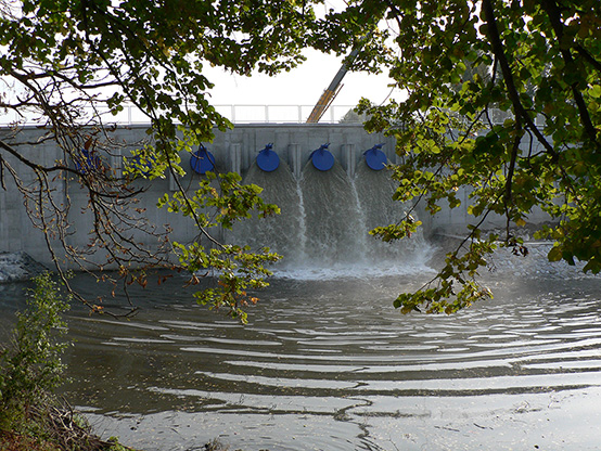 A view of the dam from the shore of the Vltava river, the first three water pumps are turned on